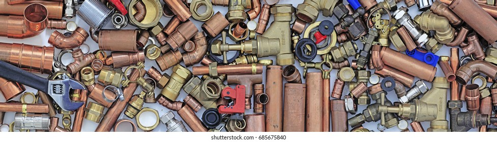 Plumber's pipes and fittings website banner Wide  random mixture of copper pipe and brass fittings ideal for use as a website header  background