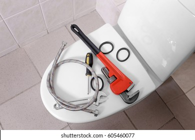 Plumber's tools on toilet at home