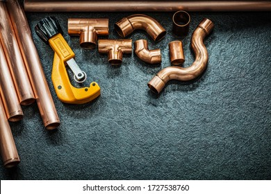plumbing concept copper pipes pipe cutter and fittings on black background