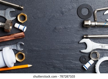 Plumbing concept. tools and pipes on a dark slate bakground