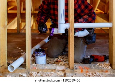 Plumbing contractor installing plastic PVC pipe in under the bathroom sink