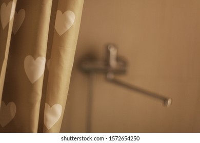 Plumbing in the house, the faucet in the bathroom in focus, in the foreground curtain with a pattern of hearts.