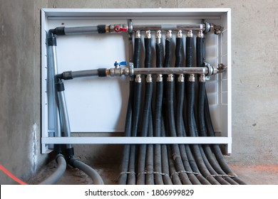 Plumbing manifold system tubing for house water distribution, control valves home water pipe, close-up human hand opening valve.