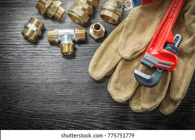 Plumbing monkey wrench pipe fittings protective gloves water valve on wooden board.