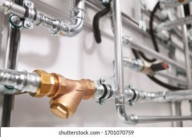 Servicio de fontanería. tubería de acero inoxidable de un sistema de calefacción en la sala de calderas. Filtro grueso de bronce