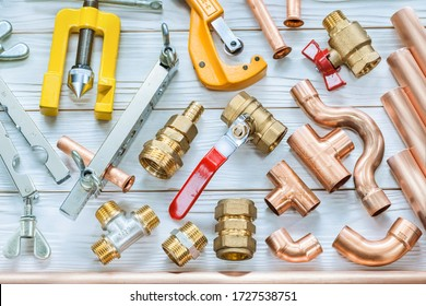 plumbing tools copper pipes pipe cutter fittings valwes flaring clamps on white wooden boards