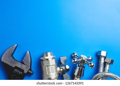 plumbing tools and equipment on blue background with copy space