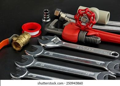 Plumbing tools on black background.