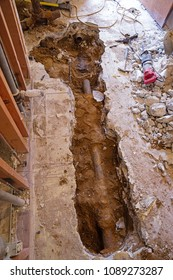 plumbing work in a home remodel with concrete slab broken up and sewer pipe cut