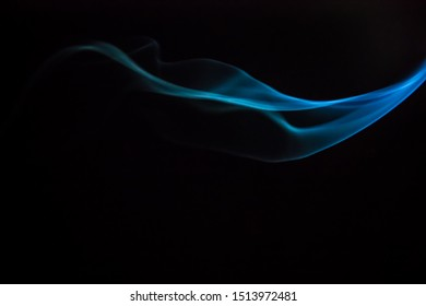 Plume of blue smoke on a black background