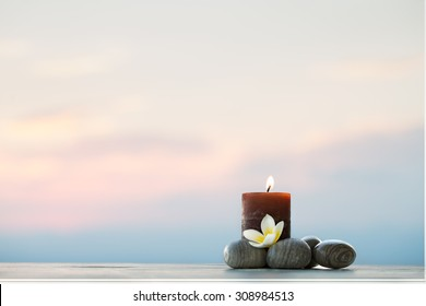 Plumeria flower, candle and stones for spa background