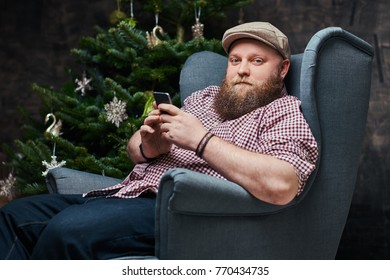 Plump bearded hipster male in a room.