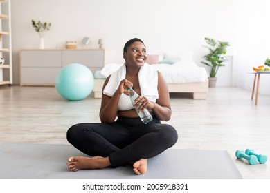 Plump black lady in sportswear sitting on sports mat with bottle of clear water at home, full length. Curvy African American woman keeping hydrated during domestic training indoors
