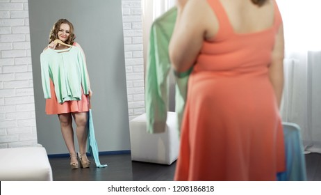 Plump girl choosing clothes in dressing room, plus size fashion, body positive