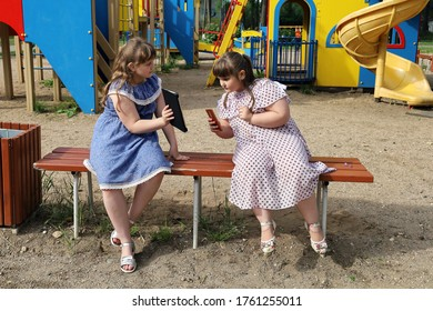 Plump girls show each other something in their smartphone and tablet. They do not play outdoor games in the playground, but are dependent on their electronic devices.