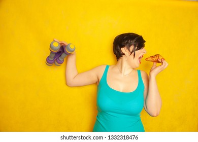 plump joyful emotional girl with short hair in a blue t-shirt tries to play sports with dumbbells to be healthy and lose weight, but can not refuse a croissant and harmful food