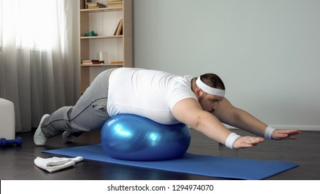 Plump male doing static exercise effort on fitness ball, desire to lose weight