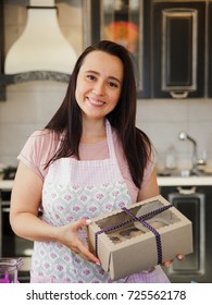 Plump woman confectioner on the kitchen. Mature woman in pastel apron holding kraft box with homemade cupcakes and smiling.