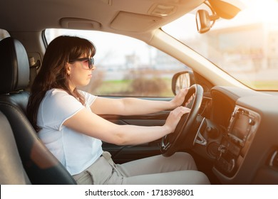Plump woman in white tshirt without seatbelt driving a car and honking on signal horn. Unsafety driving in the city traffic jam.