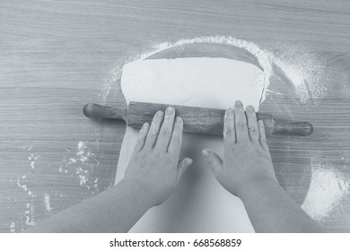 Plump women's hands work with dough on a light wooden table. Toned.