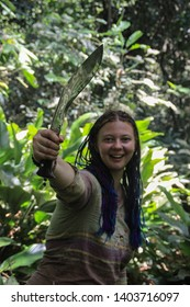 A plump young white girl traveler with blue pigtail hair in the jungle holding a machete.