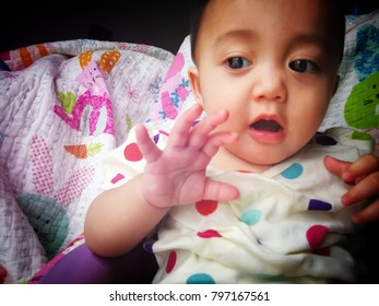 plumpy baby girl , seven months old chubby infant , dark brown eyes and black hair wear polkadot offwhite jumpsuit sit on purple seat with colorful background