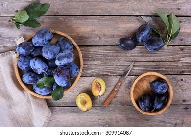 Plums in a bowl on a wooden table
