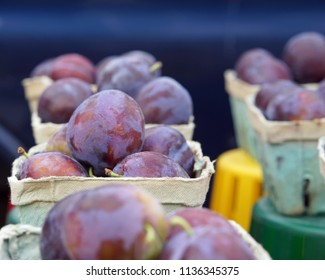 Plums in cartons on farmer's market table