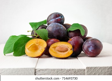 Plums on white wooden background. Half of blue plum fruit. Many beautiful plums with leaves.