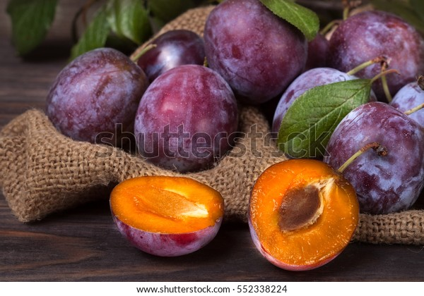 plums on the wooden background with sackcloth