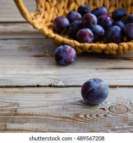 Plums on wooden background and in wicker basket.