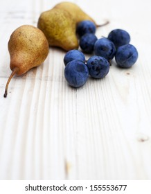 Plums and pear on wooden background