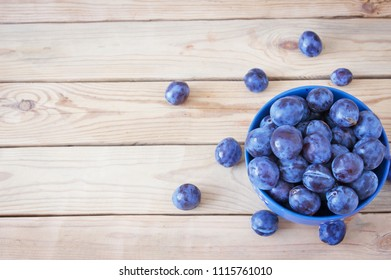 plums in plate on wooden desk