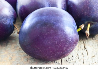 """Plums (Prunus Domestica) variety """"President"""" over a wooden table with bright ambient"""