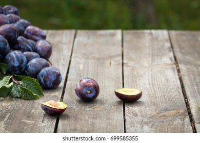 Plums scattered on old wooden table in garden.