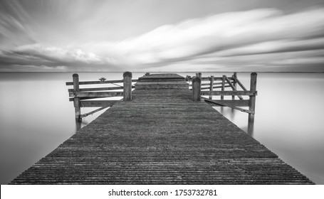 The Plunge, monochrome jetty in the Markenmeer the Netherlands during sunset.