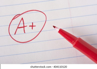 A plus (A+) grade written in red, on notebook paper with the pen sitting there.