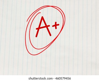 A plus (A+) grade written in red on notebook paper
