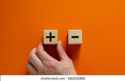 Plus or minus. Businessman holds a cubes with plus icon. Wooden cube with minus icon. Beautiful orange background. Copy space. Business and plus and minus concept.