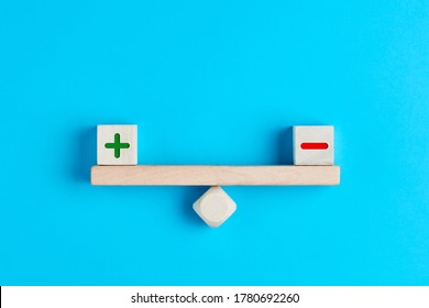 Plus and minus or positive and negative symbols on wooden blocks are in balance on a wooden seesaw. Blue background, flat lay view. Pros and cons equilibrium in decision making under uncertainity.