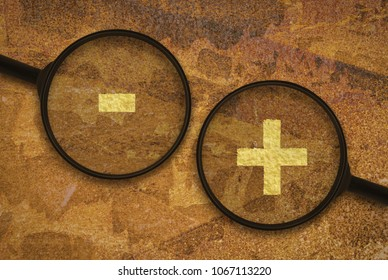 Plus and minus sign under magnifiers on grunge background
