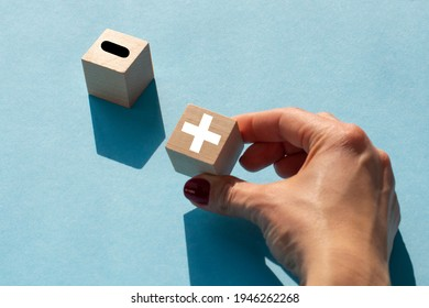 Plus or minus. Woman holds a cubes with plus icon. Wooden cube with minus icon. Beautiful blue background. Business and plus and minus concept.