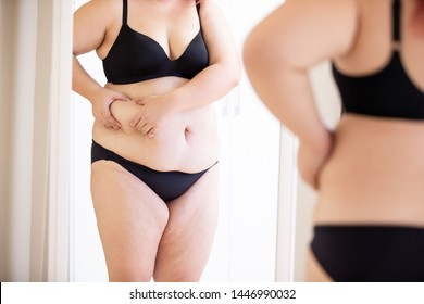 plus size asian girl pinching her potbelly and looking herself in front the mirror