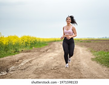 Plus size beautiful latin woman jogging on a dirt road by a canola field