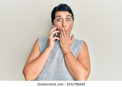 Plus size brunette woman having conversation talking on the smartphone covering mouth with hand, shocked and afraid for mistake. surprised expression