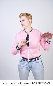 plus size caucasian girl with short haircut stands in pink sports jacket with chocolate bar in her hands and shows hate emotions for sweets. young woman wants to be healthy and slim. diet concept.