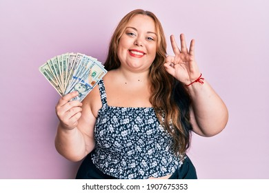 Plus size caucasian young woman holding dollars doing ok sign with fingers, smiling friendly gesturing excellent symbol