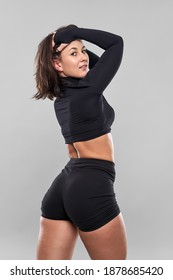 Plus size confident young woman doing fitness exercises on gray background