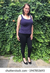 plus size curve model full length view in vest and jeans agaist ivy garden background