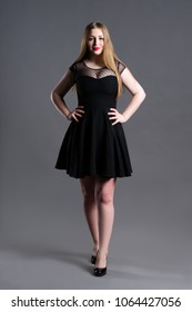 Plus size fashion model in black dress, fat woman on gray studio background, overweight female body, full length portrait